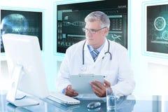 Immagine composita 3d della lavagna per appunti maschio della tenuta di medico mentre esaminando il monitor del computer Fotografie Stock Libere da Diritti