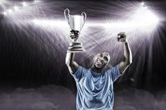 Immagine composita 3D dello sportivo felice che cerca e che incoraggia mentre tenendo trofeo Immagine Stock