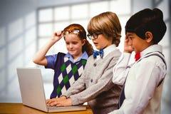 Immagine composita degli allievi che per mezzo del computer portatile Fotografie Stock