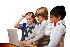 Immagine composita degli allievi che per mezzo del computer portatile Fotografia Stock