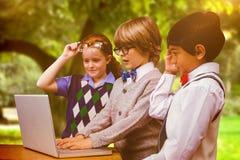 Immagine composita degli allievi che per mezzo del computer portatile Fotografie Stock Libere da Diritti