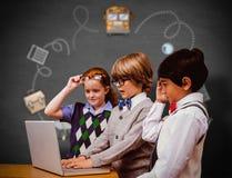 Immagine composita degli allievi che per mezzo del computer portatile Immagini Stock