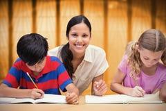 Immagine composita degli allievi d'aiuto dell'insegnante grazioso in biblioteca Immagini Stock