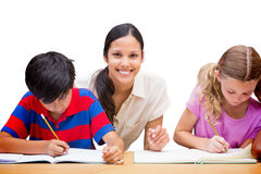 Immagine composita degli allievi d'aiuto dell'insegnante grazioso in biblioteca Immagini Stock Libere da Diritti