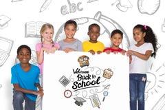 Immagine composita degli allievi elementari che mostrano carta Fotografia Stock Libera da Diritti