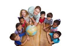 Immagine composita degli allievi svegli che sorridono intorno ad un globo in aula con l'insegnante Immagini Stock Libere da Diritti