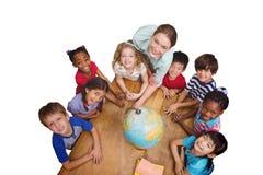 Immagine composita degli allievi svegli che sorridono intorno ad un globo in aula con l'insegnante Fotografie Stock Libere da Diritti