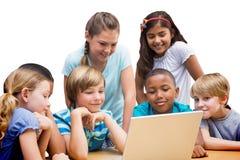 Immagine composita degli allievi svegli che utilizzano il computer della compressa nella biblioteca Fotografia Stock