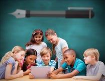 Immagine composita degli allievi svegli che utilizzano il computer della compressa nella biblioteca Immagini Stock Libere da Diritti