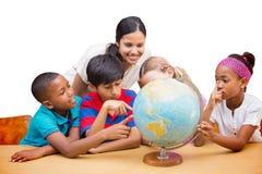 Immagine composita degli allievi svegli e dell'insegnante che esaminano globo in biblioteca Fotografia Stock Libera da Diritti