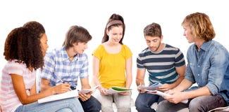 Immagine composita degli studenti di college che fanno compito Fotografie Stock Libere da Diritti