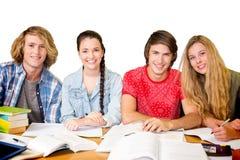 Immagine composita degli studenti di college che fanno compito in biblioteca Immagini Stock