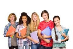 Immagine composita degli studenti di college che tengono i libri in biblioteca Fotografia Stock Libera da Diritti