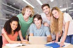 Immagine composita degli studenti di college che utilizzano computer portatile nella biblioteca Immagini Stock Libere da Diritti