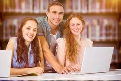 Immagine composita degli studenti di modo che per mezzo del computer portatile Immagine Stock