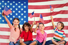 Immagine composita dei bambini con le bandiere americane Fotografie Stock Libere da Diritti