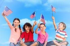 Immagine composita dei bambini con le bandiere americane Fotografia Stock