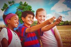 Immagine composita dei bambini felici che prendono selfie in corridoio della scuola Fotografia Stock Libera da Diritti