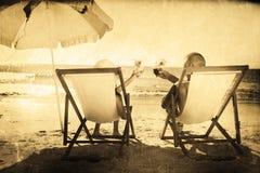 Immagine composita dei cocktail beventi delle coppie felici mentre rilassandosi sui loro sdrai Fotografie Stock Libere da Diritti