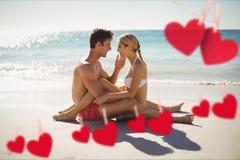 Immagine composita dei cuori rossi e delle coppie che stringono a sé sulla spiaggia fotografie stock libere da diritti