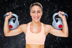 Immagine composita dei kettlebells di sollevamento del crossfitter femminile felice che esaminano macchina fotografica Fotografia Stock Libera da Diritti