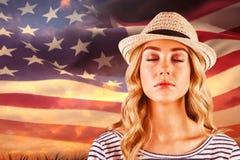 Immagine composita dei pantaloni a vita bassa biondi splendidi con il cappello di paglia Fotografia Stock Libera da Diritti