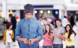 Immagine composita dei pantaloni a vita bassa che per mezzo del telefono cellulare immagine stock libera da diritti