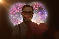 Immagine composita dei pantaloni a vita bassa geeky che sorride e che tiene la carta del cuore Immagine Stock
