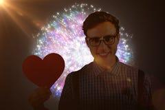 Immagine composita dei pantaloni a vita bassa geeky che tiene una carta del cuore Fotografia Stock Libera da Diritti