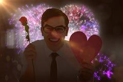 Immagine composita dei pantaloni a vita bassa geeky che tiene una carta del cuore e della rosa rossa Fotografie Stock Libere da Diritti