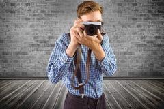 Immagine composita dei pantaloni a vita bassa geeky che tiene una retro macchina fotografica Immagini Stock Libere da Diritti