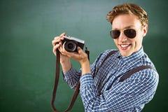 Immagine composita dei pantaloni a vita bassa geeky che tiene una retro macchina fotografica Immagine Stock Libera da Diritti