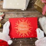 Immagine composita del Babbo Natale che tiene un cartello rosso Fotografia Stock