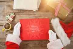 Immagine composita del Babbo Natale che tiene un cartello rosso Immagini Stock