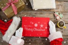 Immagine composita del Babbo Natale che tiene un cartello rosso Immagine Stock Libera da Diritti