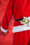 Immagine composita del Babbo Natale che tiene un contenitore di regalo dietro il suo indietro Fotografia Stock
