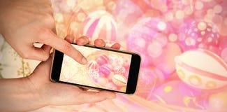 Immagine composita del canestro con le uova di Pasqua dipinte con le piante Fotografia Stock