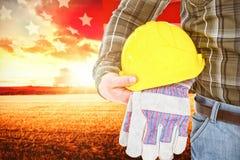 Immagine composita del casco e dei guanti della tenuta del lavoratore manuale Fotografie Stock Libere da Diritti