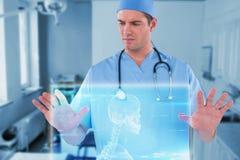 Immagine composita del chirurgo che finge di utilizzare schermo digitale futuristico 3d Fotografia Stock