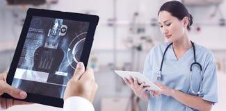 Immagine composita del chirurgo che utilizza compressa digitale con il gruppo intorno alla tavola nell'ospedale Immagini Stock