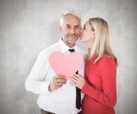 Immagine composita del cuore bello della carta della tenuta dell'uomo che ottiene un bacio dalla moglie fotografia stock libera da diritti