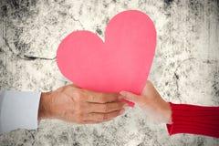 Immagine composita del cuore della tenuta delle coppie Immagini Stock