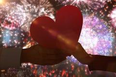 Immagine composita del cuore della tenuta delle coppie Immagini Stock Libere da Diritti