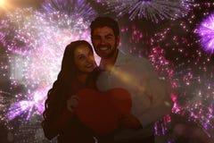 Immagine composita del cuore felice della carta della tenuta delle coppie Fotografie Stock