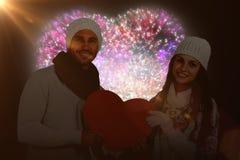 Immagine composita del cuore sorridente della carta della tenuta delle coppie Fotografia Stock Libera da Diritti
