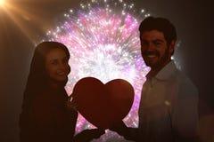 Immagine composita del cuore sorridente della carta della tenuta delle coppie Fotografie Stock