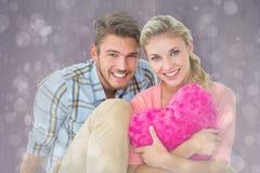 Immagine composita del cuscino di seduta del cuore della tenuta delle giovani coppie attraenti Fotografia Stock Libera da Diritti