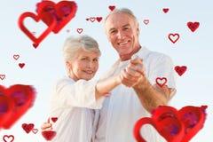 Immagine composita del dancing senior delle coppie sulla spiaggia Immagini Stock Libere da Diritti