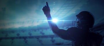 Immagine composita del giocatore di football americano in casco che indica verso l'alto immagine stock libera da diritti