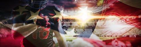 Immagine composita del giocatore di football americano in casco che tiene la palla di rugby con le armi nell'aria fotografie stock